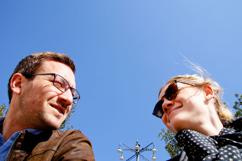 Low angle view of smiling couple against clear blue sky