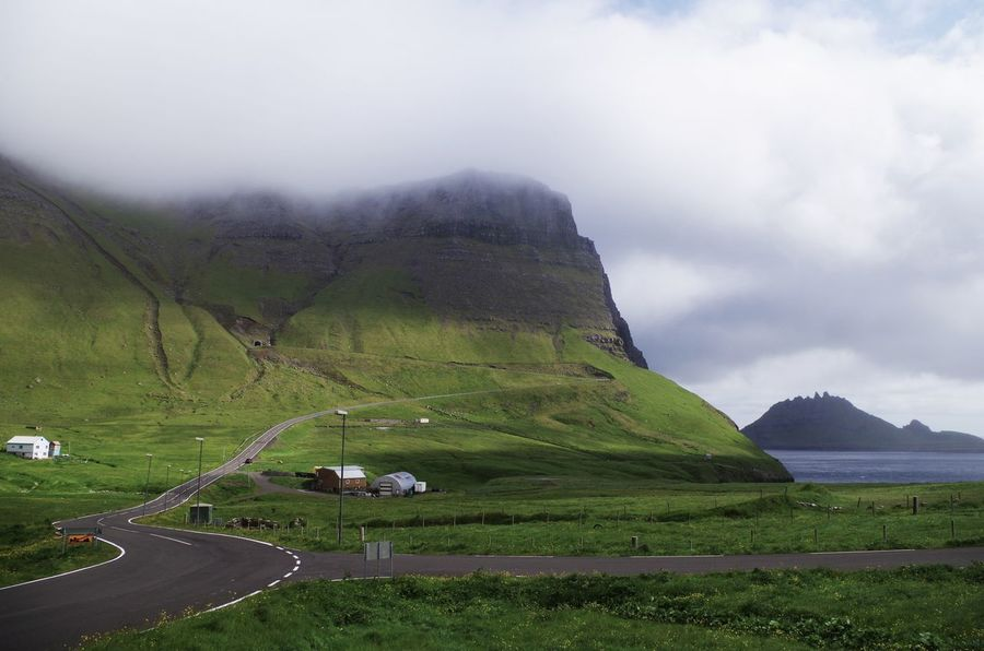 Gasadalur with the distinctive Tindholmur island in the background. Agriculture Cloud Cloud - Sky Clouds Cloudy Day Fabulous Farm Faroe Islands Fog Gasadalur Grass Green Houses Landscape Landscapes Magical Mountain Nature No People Outdoors Scenery Steep Tindhólmur Winding Road