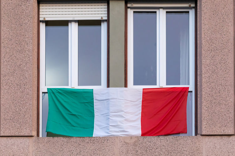 The italians locked up in the quarantined house display the rainbow flag on the windows