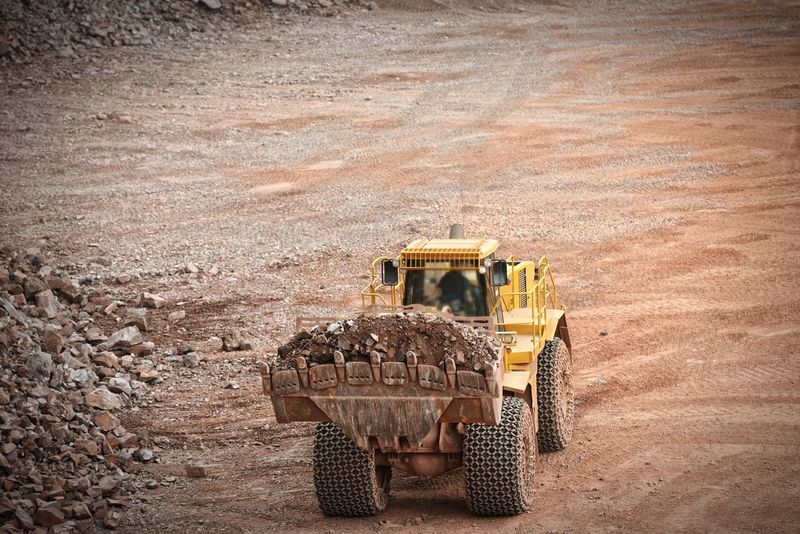earth mover carrying rocks in a stone pit, quarry Radlader Open Pit Mine Quarry Mining Mine Bergbau Steinbruch Porphyry Pit Excuvator Rock Formation Construction Materials Bagger