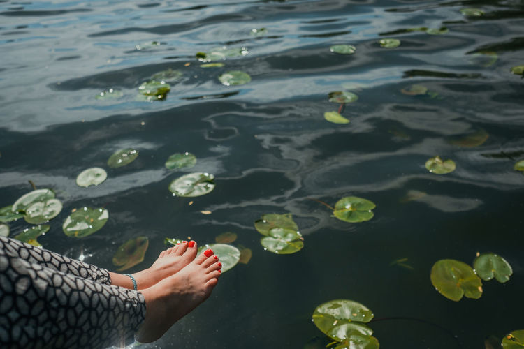 Low section of woman floating on lake