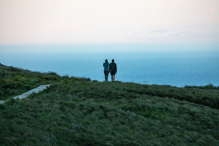 Rear view of people standing on cliff against sea