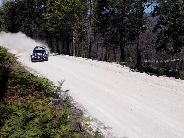 Racecar on dirt road with dust