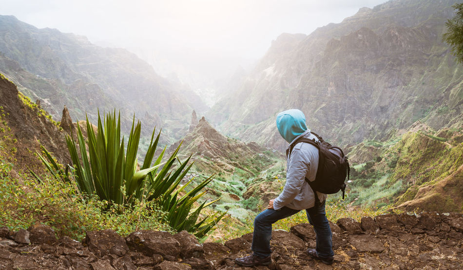 Traveler with backpack looking over the rural landscape with mountain peaks and ravine in dust air on the path from Xo-Xo Valley. Santo Antao Island, Cape Verde Breathtaking Trekking Xo-xo Adventure Agave Beauty In Nature Day Hiking Lifestyles Men Mountain Mountain Range Nature Non-urban Scene One Person Outdoors Peak Plant Real People Rear View Scenics - Nature Tranquil Scene Tranquility Valley Yucca Plant Adventures In The City