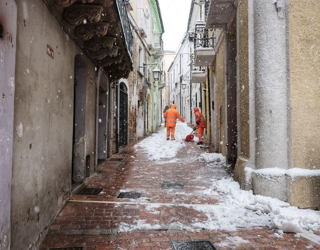 workers shovel snow in the historic center Clearing Uniforms Architecture Built Structure Cold Temperature Day Indoors  Manual Worker Men People Real People Removal Shovel Shoveling Snow Snowing Street The Way Forward Walking Winter