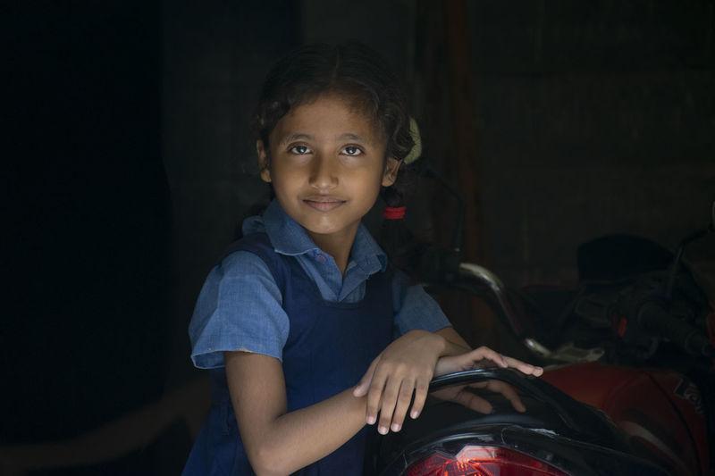 Portrait of girl wearing school uniform standing by motorcycle