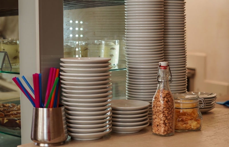 Stack of plates by food on table