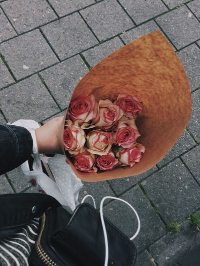 Cropped image of person holding rose bouquet on paved footpath