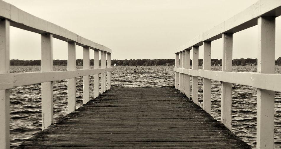 Footbridge over sea against clear sky