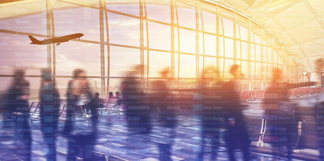 Digital composite image of silhouette people standing against window at the airport