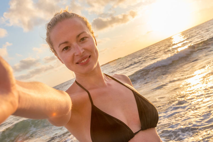 Portrait of smiling woman on beach during sunset