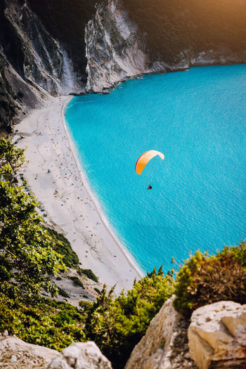 Myrtos Beach, Kefalonia Island, Greece. Figure of a parachutist skydiver with orange parachute against a blue lagoon bay beach Water Adventure Sea Rock Extreme Sports Sport Beauty In Nature Scenics - Nature Nature Rock - Object Solid Land Freedom Beach Holiday Plant Day Cliff Outdoors Activity Hobby Paragliding Parasite Attitude Glider