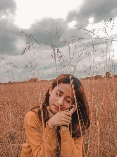 Portrait of beautiful young woman on field against sky