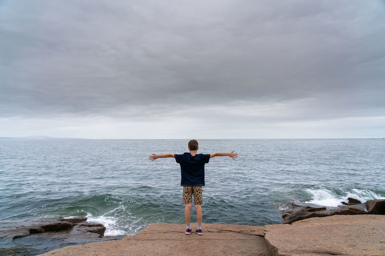 I'm this big Arms Outstretched Arms Raised Beauty In Nature Casual Clothing Cloud - Sky Freedom Horizon Over Water Human Arm Leisure Activity Lifestyles Limb One Person Outdoors Real People Rear View Rock Rock - Object Scenics - Nature Sea Sky Standing Water