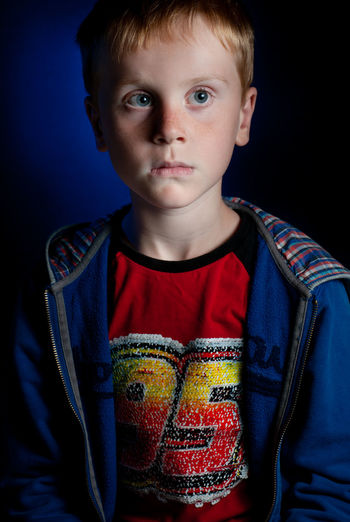 Portrait of boy standing against black background