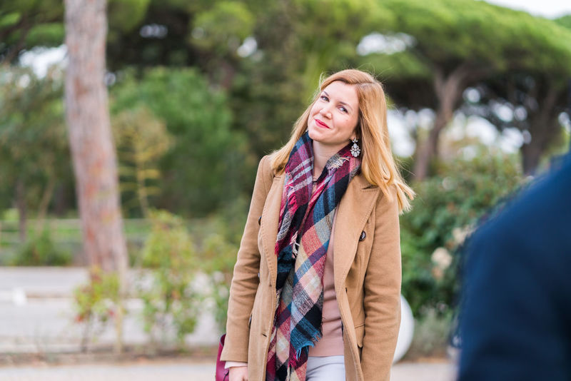 Adult Beautiful Woman Blond Hair Casual Clothing Day Focus On Foreground Front View Happiness Jacket Leisure Activity Lifestyles Long Hair One Person One Woman Only One Young Woman Only Only Women Outdoors Overcoat Real People Scarf Smiling Standing Tree Young Adult Young Women