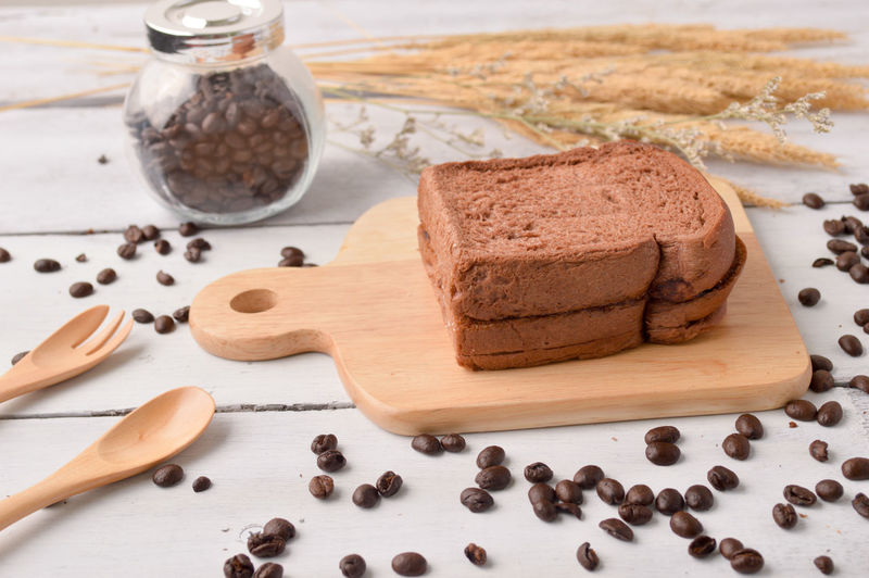 High Angle View Of Breads And Coffee Beans On Table