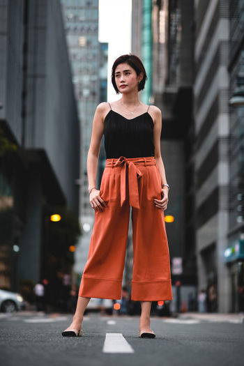 Full length of woman looking away while standing on road in city