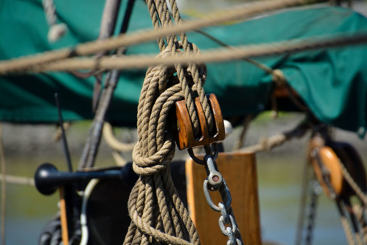 Close-up of rope tied up on metal chain