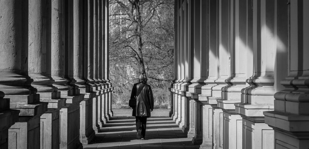 Full Length Rear View Of Woman Walking By Colonnade