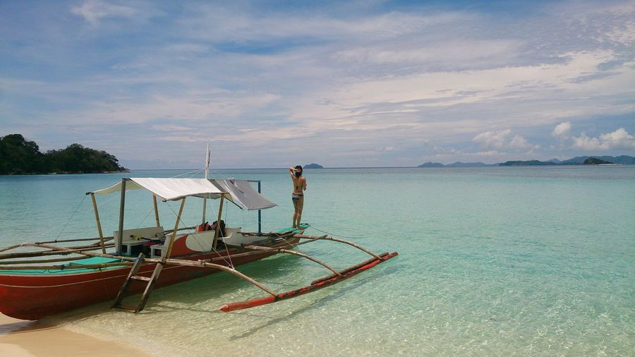 Rear View Of Woman Standing On Outrigger Canoe At Palawan