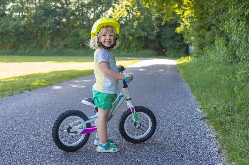 Full length portrait of cute boy with bicycle standing on road