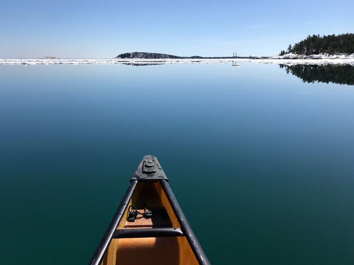 Flat, glassy Lake Superior water. An ice shelf a half mile out created a barrier against the waves leaving the interior lagoon a smooth glassy finish that created some incredible reflections. EyeEm Selects Water Nature Tranquility No People Scenics - Nature Sky Tranquil Scene Reflection Day Transportation Beauty In Nature Outdoors Waterfront Nautical Vessel