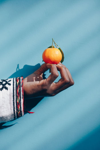 Cropped hand holding orange against wall