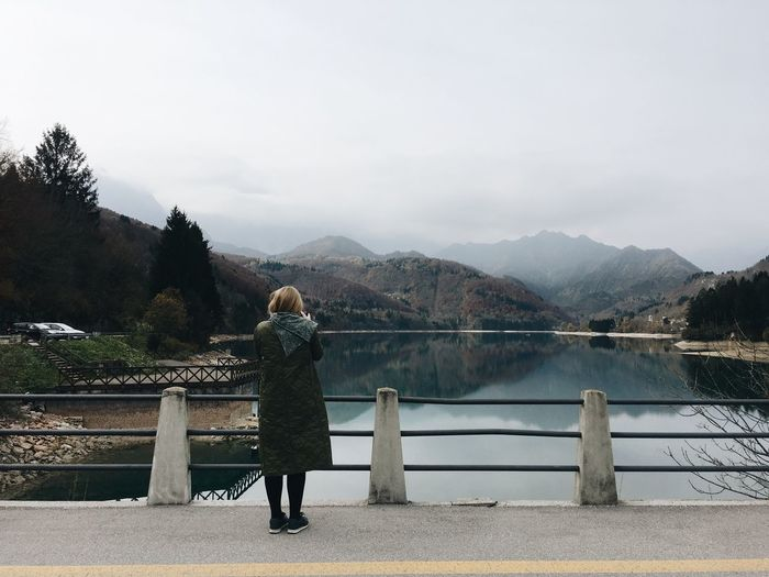 Mountain Railing Rear View Nature Real People Lake Beauty In Nature One Person Mountain Range Outdoors Bridge - Man Made Structure Scenics Standing Water Full Length Tranquil Scene Day Women Sky Leisure Activity
