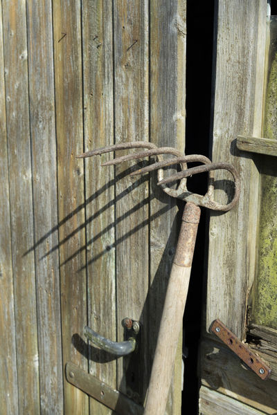 An old spading fork positioned against an old door left ajar, casts a creepy shadow on it Agriculture Fear Fork Garden Tools Spading Fork Creepy Old House Pitchfork Shadow Tool