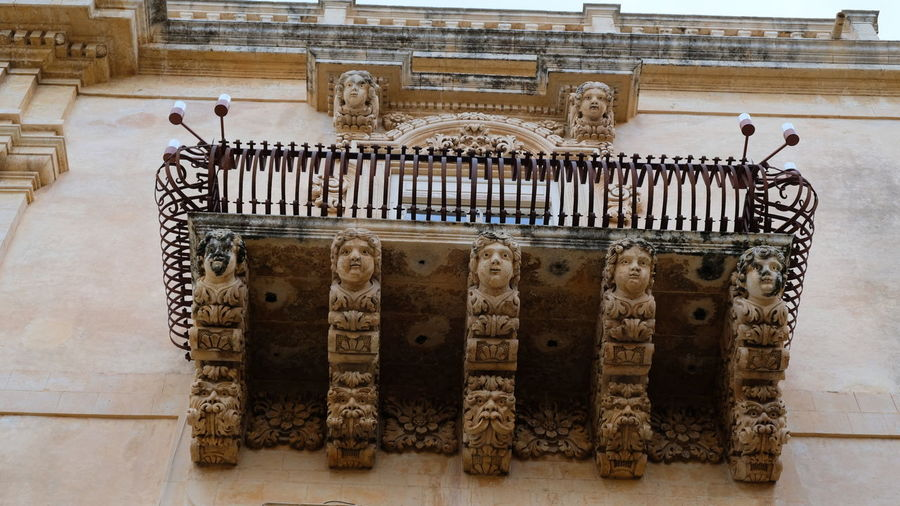City of Noto. Province of Syracuse, Sicily. One of the spectacular balconies of the Palazzo Nicolaci. The entire city of Noto is known as one of the most remarcable examples of the sicilian baroque style. Noto,sicily Syracuse  Sicily, Italy Sicilian Baroque Architecture Detailed Close-up Elaborate Balcony Rare Peculiar Palazzo Nicolaci Sandstone Faces Childs