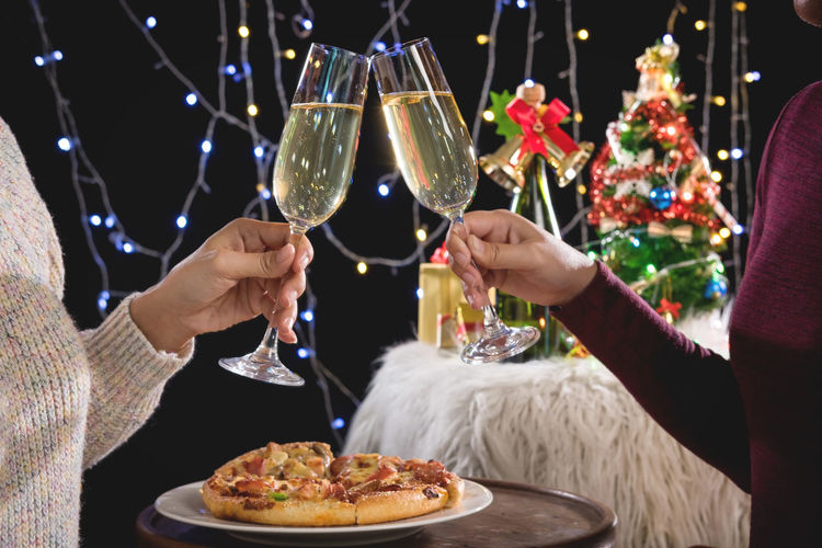 Midsection of friends toasting champagne flute during christmas