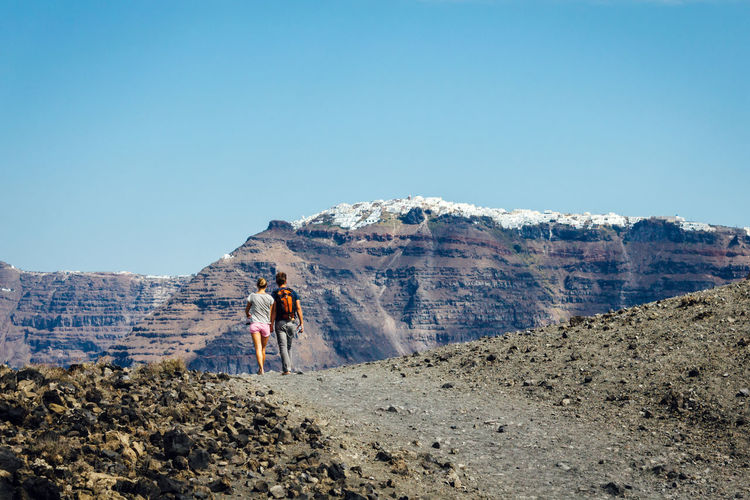 Rear view of man and woman walking against mountain