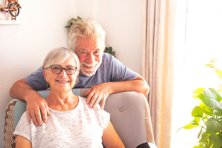 Senior adult couple looking at camera. Two caucasian people. Gray and white hair. Bright light from window. Happy and relaxed retirement. Natural plants in background 70 Years Activity Adult Aged Armchair Background Beard Bright Casual Caucasian Connection Couple Decoration Domestic Elderly Emotion Enjoying Eyeglasses  Grandparents Gray Hair Hands Home Hug Inside Light Love Man Mobile Phone Natural News Old Pensioner Photo Plant Positivity Retired Retirement Senior Serene Sitting Smiling Sun Sunlight Tablet Technology Tenderness White Window Woman Togetherness