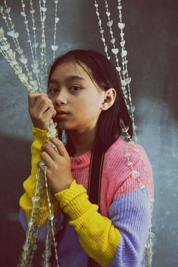 Portrait of girl holding beaded curtain while standing at home