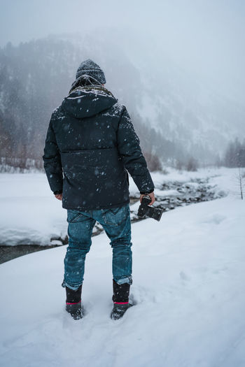 Rear view of man standing on snow field