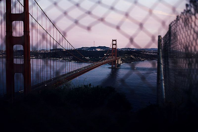 Golden gate bridge over san francisco bay seen through chainlink fence at sunset