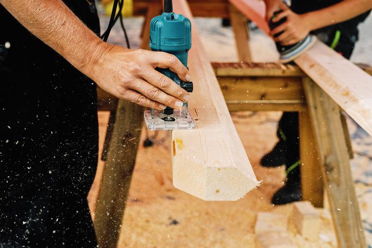 People polishing wood with sanding machine