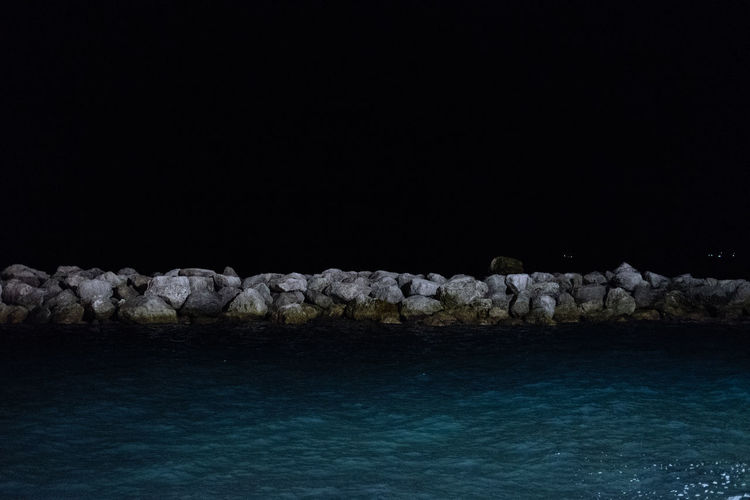 Rocks by sea against clear sky at night