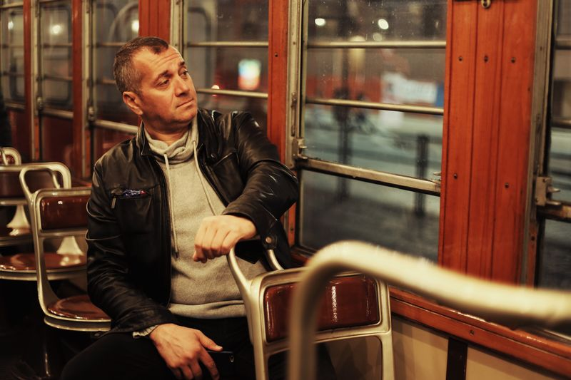 Man looking away while sitting in train at night