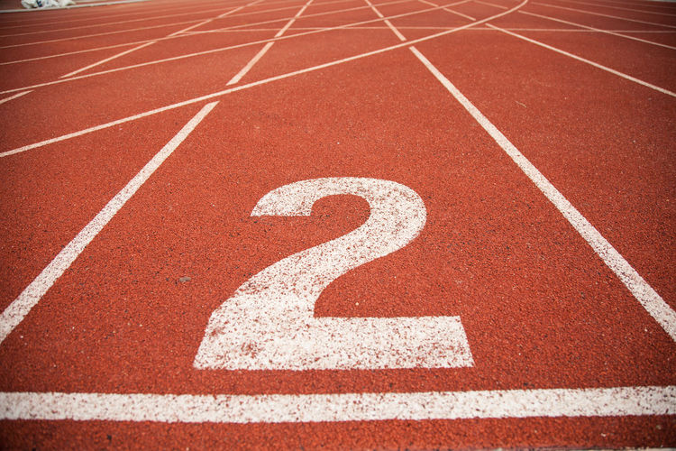 Close-up Competition Competitive Sport Curve In A Row No People Number Outdoors Red Running Running Track Sport Sports Race Sports Track Stadium Starting Line Track And Field Track Event White Color