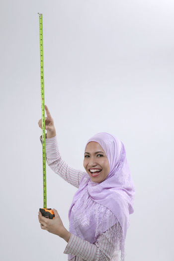 malay woman holding tape measure Happiness Industry Measuring Renovation Worker Adviser Builder Career Carpenter Contractor Equipment Headscarf Headwear Hijab Holding Length Lifestyles Malay Malaysia Occupation One Person Smiling Studio Shot Tape Measure Tudung