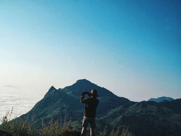 Rear view of man photographing while standing on mountain against clear sky