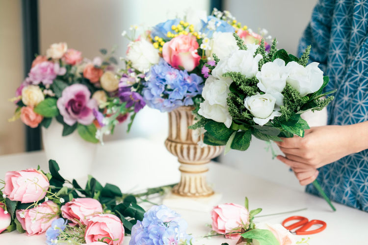 Midsection Of Woman Arranging Flowers In Vase On Table