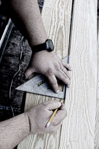 Hands of carpenter measuring plank at workshop