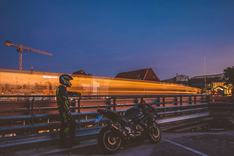 Side view of biker standing by motorcycle against light trails in city at dusk