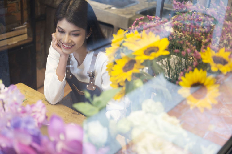 Young woman sitting at flower shop seen through window