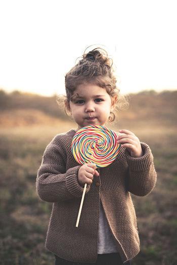 Portrait of cute girl with lollipop standing on field