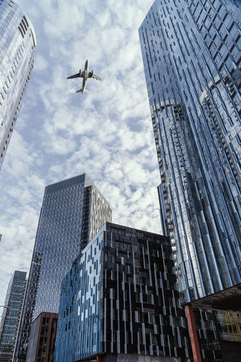Low angle view of airplane flying above modern buildings