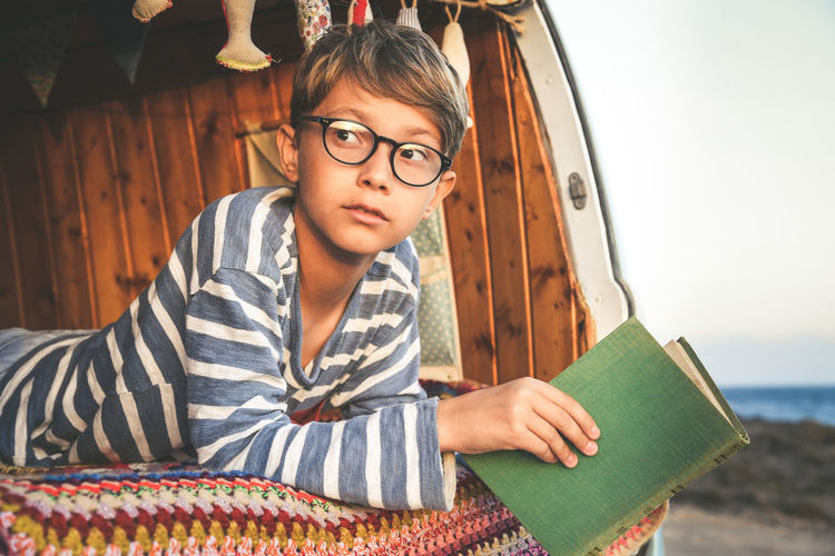 Young boy on retro mini van transport read a book Life inspiration concept with family minivan adventure trip reading a blast relax moment Student doing homework outdoor camping holiday near the sea One Person Glasses Eyeglasses  Holding Leisure Activity Child Book Lifestyles Childhood Publication Casual Clothing Young Adult Front View Real People Portrait Sitting Focus On Foreground Striped Hairstyle Contemplation